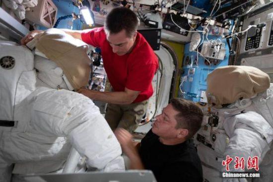 资料图:2020年6月24日报道,美国宇航员克里斯托弗・卡西迪(左)和罗伯特・本肯将于6月26日和7月1日从国际空间站出发进行两次太空行走,以便更换电池。图为二人在准备太空服。图片来源:视觉中国