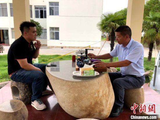 林昆佑(左)和家人讨论最近的生意情况。 朱晓颖 摄