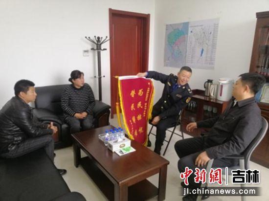 郑丽(左二)给薛春龙(右)送来锦旗。长春新区城市管理局/供图