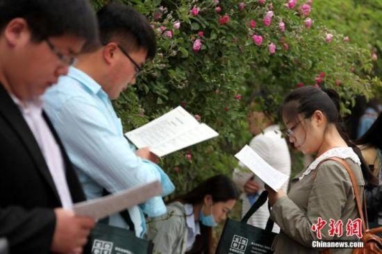 资料图:考生在公务员考试考场外复习。中新社发 吉 �� 摄 图片来源:cnsphoto