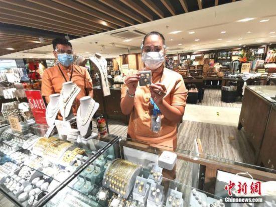 8月23日,马尼拉首都CBD马卡蒂商圈著名的国礼店KULTURA,营业员戴着口罩、面罩向顾客推销珠宝。 中新社记者 关向东 摄