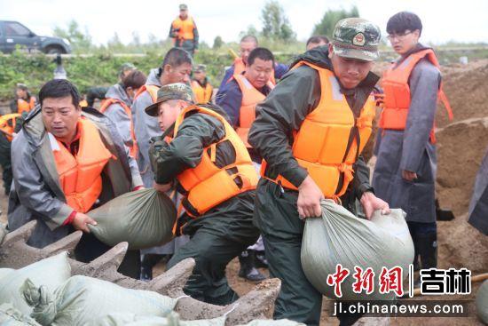 """驻延某部官兵与驻地群众一同搭建堤坝,共同抵御台风""""狮子山""""。延吉市委宣传部/供图"""