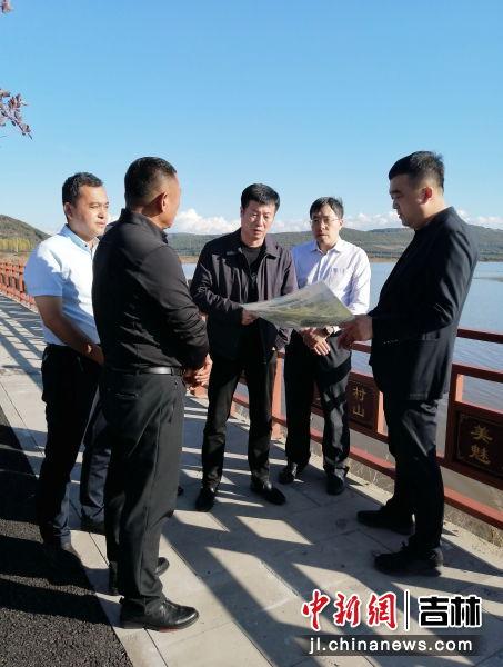 孙羚哲(右一)介绍河湖沿岸清理情况。敦化市委宣传部/供图