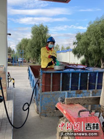 中国石油员工为购油农户加油。陆迎艳/摄