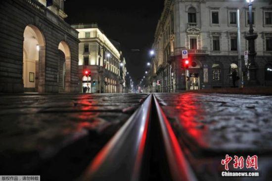 当地时间10月25日凌晨,意大利北部米兰,斯卡拉歌剧院前的一条空街被红灯照亮。
