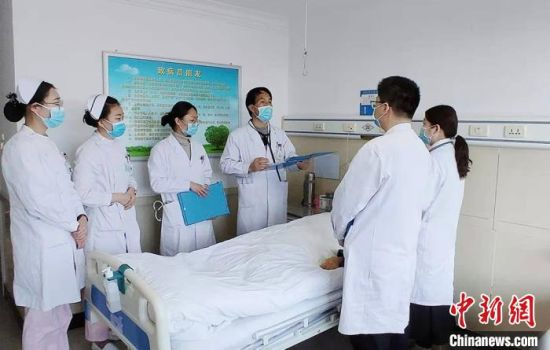 周国庆和医护工作人员询问住院病人病情。 高康迪 摄