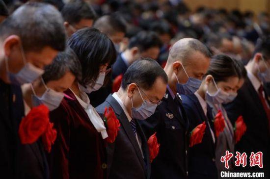 全场参会人员向抗击新冠肺炎疫情牺牲烈士和逝世同胞默哀。 李南轩 摄