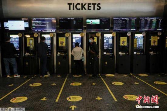 资料图:当地时间2020年7月1日,马来西亚吉隆坡,电影院重新开放,观众用自动售票机买电影票。