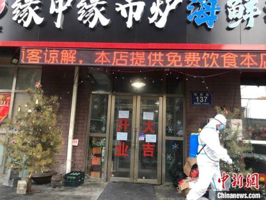 一位防疫人员路过王撼东的店。 孙博妍 摄