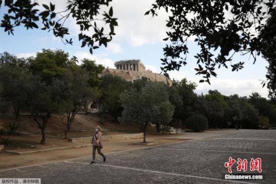 资料图:希腊雅典,一名戴口罩女子经过帕特农神庙。