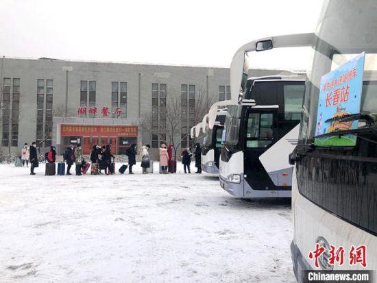 """吉林大学2021年""""情暖冬日・学生返乡送站班车""""15日开通,学生有序乘车。 郭佳 摄"""