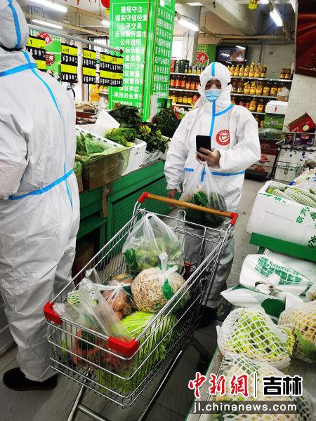 青年志愿者在超市分拣居民订单。