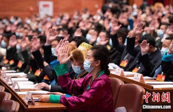 1月24日,西藏自治区第十一届人民代表大会第四次会议上代表们举手表决《西藏自治区国家生态文明高地建设条例(草案)》。中新社记者 何蓬磊 摄