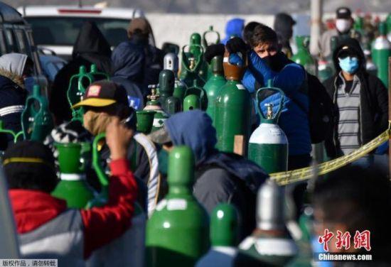 当地时间2020年7月23日,秘鲁第二大城市阿雷基帕,新冠肺炎患者的家属排队给医用氧气瓶充电。