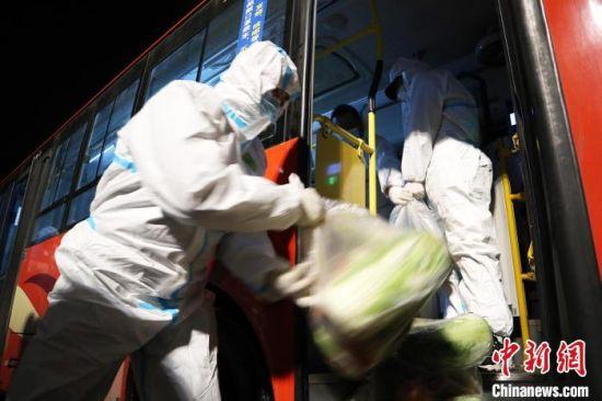 1月25日午夜,吉林省通化市,防疫人员为隔离居民运送生活物资。 苍雁 摄