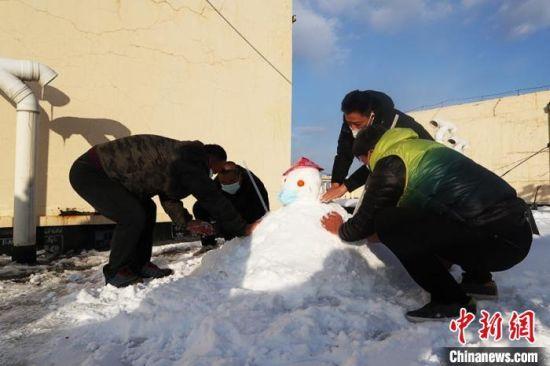 南方客人在酒店楼顶堆雪人 苍雁 摄
