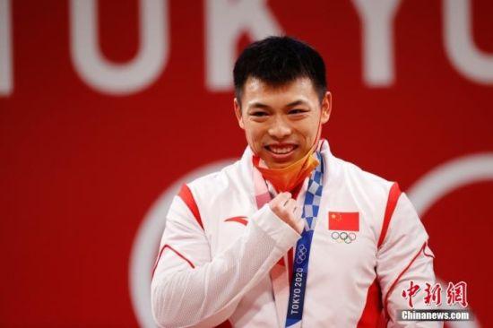 北京时间7月25日晚,在东京奥运会男子举重67公斤级比赛中,中国选手谌利军以抓举145公斤、挺举187公斤、总成绩332公斤夺冠,打破挺举和总成绩奥运纪录的同时,也为中国体育代表团摘得本届奥运会的第六金。图为谌利军在颁奖仪式上摘下口罩。 中新社记者 韩海丹 摄