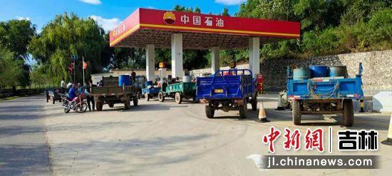 中国石油吉林通化销售分公司杉松岗加油站前,农户在工作人员的引导下排队加油。崔再菊/供图